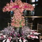 Orchids arranged to cover pink parasol umbrellas in NYC arrangement